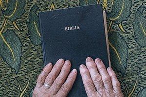 Bibel mit Hand berühren